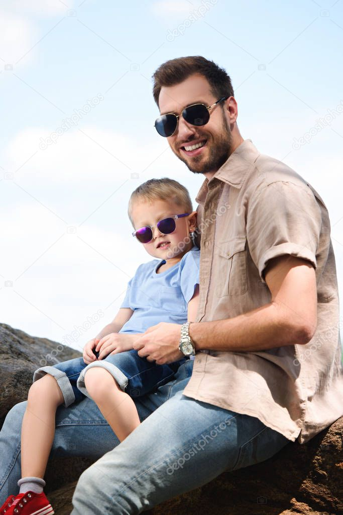 happy father and son in sunglasses looking at camera at park