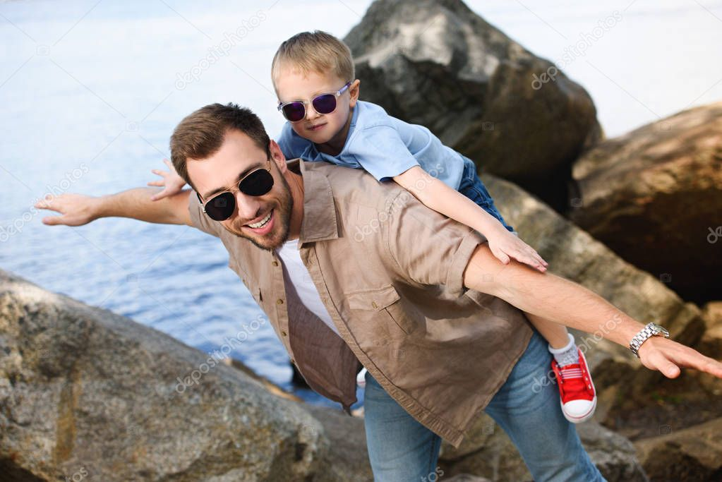happy father giving piggy back to son near lake at park
