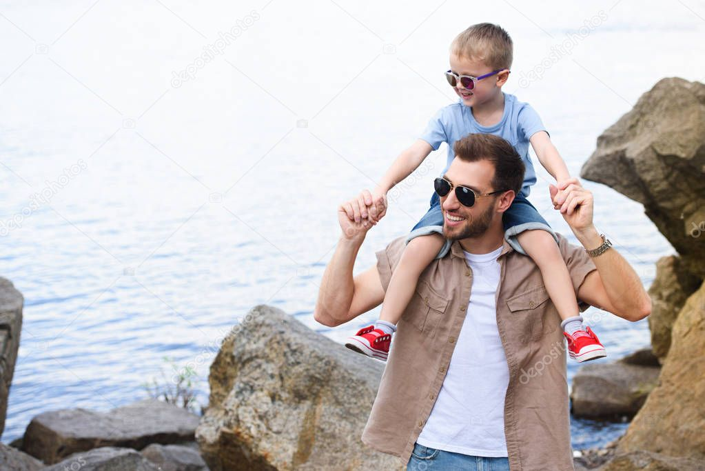 smiling father holding son on shoulders and they looking away at park