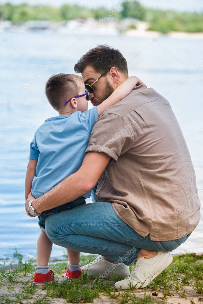 father and son hugging and touching with noses near river at park