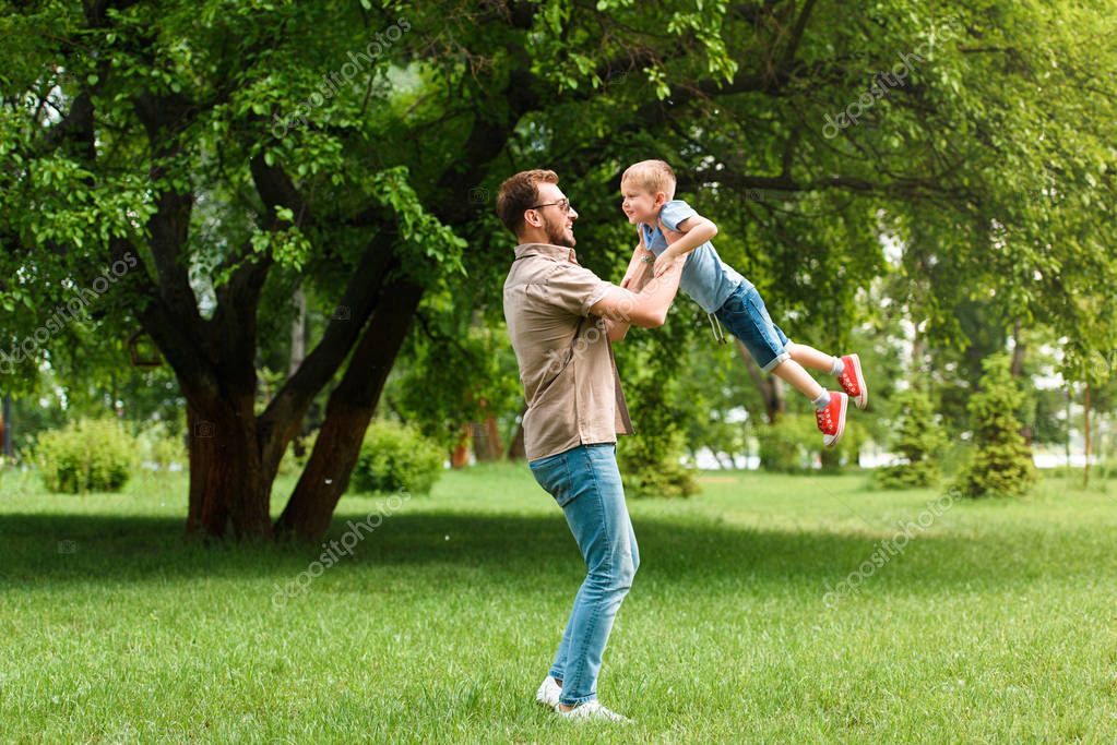 side view of father spinning around son and they having fun at park