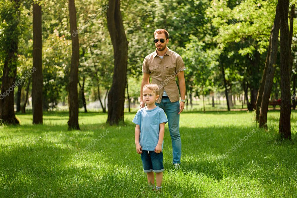 father and son standing on grass in park and looking away