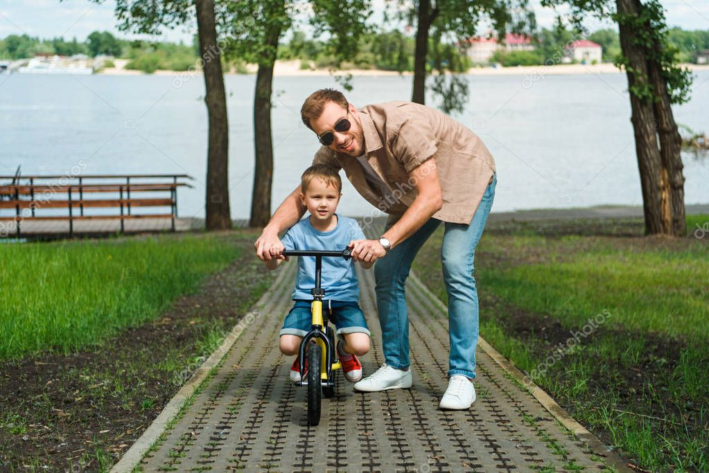 father helping son riding small bike on road near river