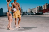 Fotografie cropped shot of young couple in beach clothes with volleyball ball on parking