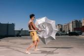 Fotografie schöner junger Mann ohne Hemd mit Sonnenschirm auf dem Parkplatz