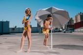 Fotografie mladý atraktivní pár s deštníkem v plavky opalování na parkování
