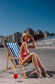 Photo stylish young woman relaxing in sun lounger on parking