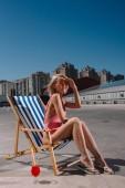 stilvolle Entspannung im Liegestuhl auf dem Parkplatz junge Frau