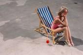 Fotografie Erhöhte Ansicht der glückliche junge Frau sitzt im Liegestuhl auf asphalt