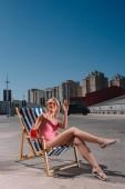 Fotografie glückliche junge Frau sitzt auf der Sonnenliege mit Cocktail im Glas auf dem Parkplatz