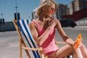 Fotografie attraktive junge Frau in Rosa Badeanzug sitzt auf der Sonnenliege und Sonnencreme eincremen auf dem Parkplatz