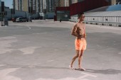 giovane bello senza camicia in pantaloncini con cocktail di nuoto sul parcheggio