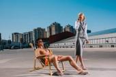 Fotografie hübscher junger Mann entspannt auf Sonnenliege während seiner Chefin im Anzug neben ihm und Gespräch per Telefon auf Parkplatz