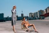 Fotografie attraktive junge Mann entspannt auf Sonnenliege während seiner Chefin im Anzug neben ihm und Gespräch per Telefon am Parkplatz
