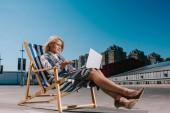 Fotografie Verrückter junge geschäftsfrau in Abendgarderobe im Liegestuhl sitzen und Laptop auf Parkplatz