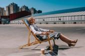 Fotografie glückliche junge geschäftsfrau in Abendgarderobe entspannen im Liegestuhl auf dem Parkplatz
