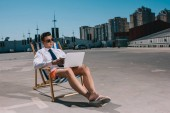 Fotografie hübscher junger Geschäftsmann in kurzen Hosen arbeiten mit Laptop sitzend auf Sonnenliegen auf Parkplatz