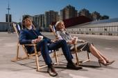 Fotografie Junge Geschäftsleute entspannend auf Sonnenliegen mit Pappbecher Kaffee auf Parkplatz