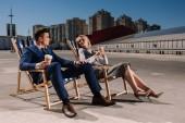 Fotografie Junge glücklich Geschäftsleute entspannend auf Sonnenliegen mit Kaffee bis zum Parkplatz gehen