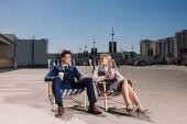 Junge Geschäftsleute, entspannen Sie sich auf Liegestühlen mit Kaffee bis zum Parkplatz gehen