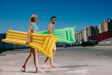 attractive young couple in beach clothes with inflatable beds walking on parking