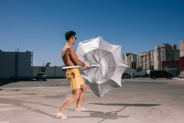 handsome young shirtless man with beach umbrella on parking
