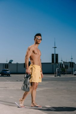 sportive young shirtless man with flippers on parking