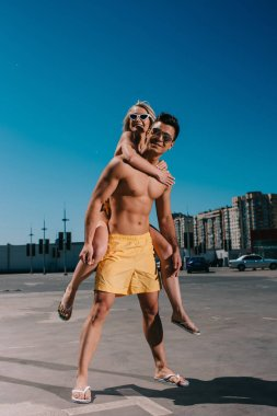 young attractive woman piggybacking on boyfriend on parking