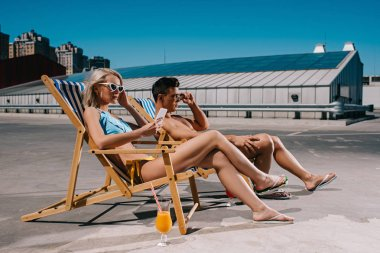 young couple relaxing on sun loungers relaxing on parking