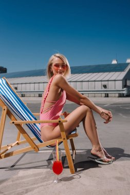 side view of smiling young woman in swimsuit sitting in sun lounger on parking