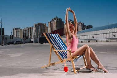 beautiful young woman stretching while relaxing in sun lounger on parking