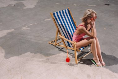 high angle view of happy young woman sitting in sun lounger on asphalt
