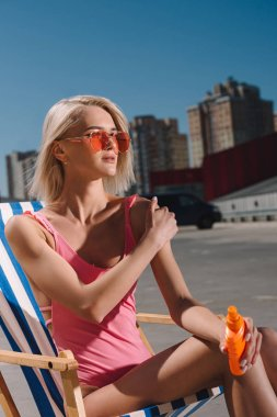 close-up portrait of young woman in pink swimsuit sitting on sun lounger and applying sunscreen lotion on parking