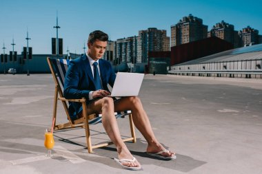 handsome young businessman in shorts and jacket working with laptop while sitting on sun lounger on parking