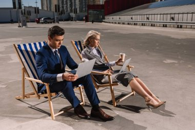 young business people working with laptop while sitting on sun loungers on parking