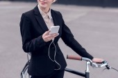 Fotografie cropped shot of businesswoman in earphones with smartphone standing near retro bicycle on street