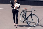 Fotografie partial view of businesswoman with documents walking on street with bicycle parked behind