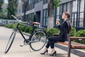 Fotografie side view of young businesswoman with coffee to go resting on bench with retro bicycle parked near by