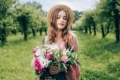 Fotografia Ritratto di giovane donna in cappello con il mazzo di fiori in mani nel parco