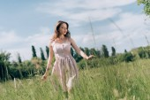 Fotografie young pensive woman in stylish dress with long hair walking in meadow alone