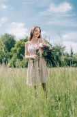 beautiful smiling woman holding bouquet of flowers while standing in field alone