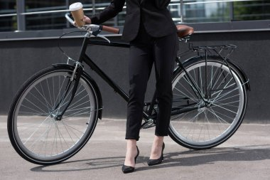cropped shot of businesswoman in suit with disposable cup of coffee standing near retro bicycle on street