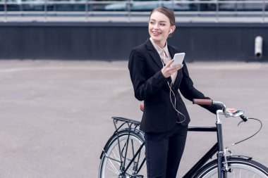 portrait of smiling businesswoman in earphones with smartphone standing near retro bicycle on street