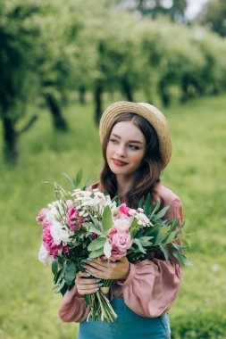portrait of beautiful pensive woman in hat with bouquet of flowers in park
