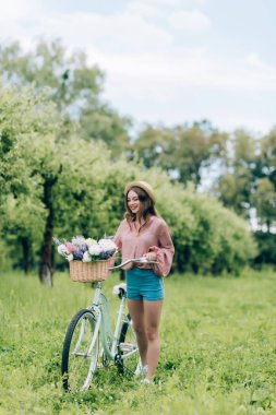 Young smiling woman with retro bicycle with wicker basket full of flowers in forest stock vector