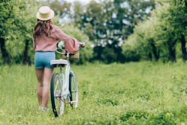 back view of young woman with retro bicycle with wicker basket full of flowers in forest