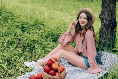 young smiling woman talking on smartphone while resting on blanket with wicker basket full of apples in park