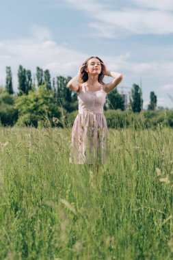 portrait of young beautiful woman in stylish dress standing in meadow alone