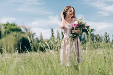 portrait of beautiful young woman holding bouquet of flowers while standing in field alone