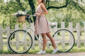 Fotografia ritagliata colpo della donna alla moda in vestito con la retro bicicletta con cestino di vimini pieno di fiori alla campagna